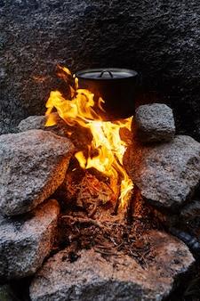 De mens bouwde een kampvuur in de bossen in de natuur. overleef in de bergen in het bos, kook in een pan boven een kampvuur. man in camouflage kokend water op vreugdevuur, overleven. open haard gemaakt van stenen
