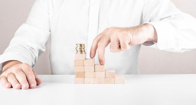 De mens bouwt een ladder van houten blokken met daarop een stapel munten