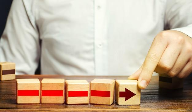 De mens bouwt een pijl uit blokken. bedrijfsontwikkeling, groeiprocesconcept.