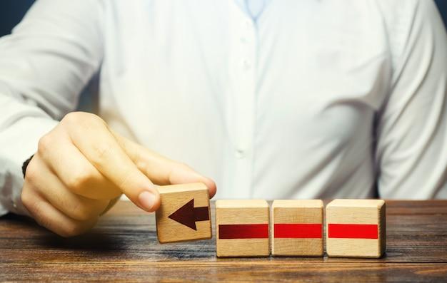 De mens bouwt een rode pijl uit blokken. bedrijfsontwikkeling, groeiprocesconcept.