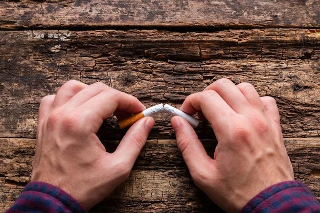 De mens breekt sigaret op houten
