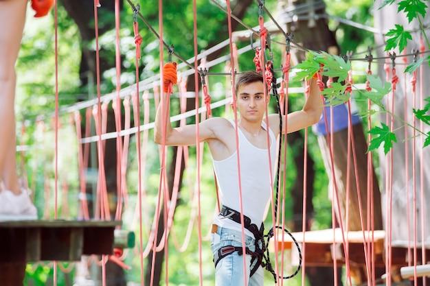 De mens brengt zijn vrije tijd door in een touwenparcours. man bezig met touwpark.