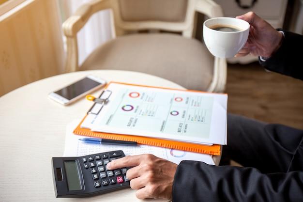 De mens die calculator gebruiken en schrijft maakt nota met berekent en drinkt koffie op het werk.