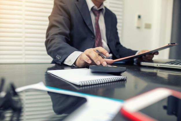 De mens die calculator gebruiken en schrijven maakt nota met in het bureau berekenen.