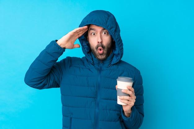 De mens die de winterjas draagt en een meeneemkoffie over geïsoleerde blauwe muur houdt heeft net iets gerealiseerd en heeft de oplossing voor ogen