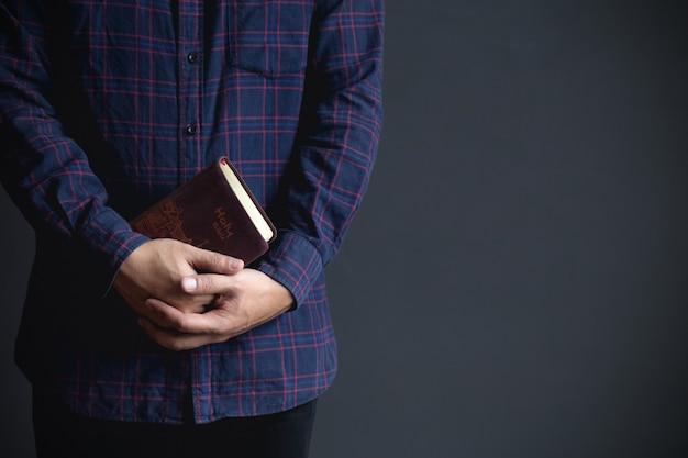 De mens die een bijbel houden, gelooft concept.copy-ruimte
