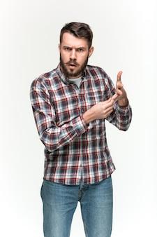 De mens die een geruit overhemd draagt kijkt pouter met een denkbeeldig voorwerp in zijn handen. over witte ruimte