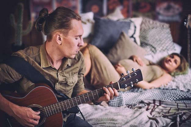 De mens die een gitaar speelt en zijn zwangere vrouw liggen op een bed in een zolderruimte