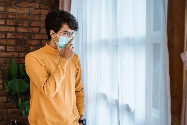 De mens die een masker draagt kijkt droevig wanneer het houden van een wekker
