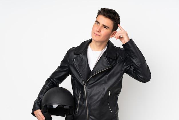De mens die een motorfietshelm houden die op wit wordt geïsoleerd dat twijfels heeft en met gezichtsuitdrukking verwart