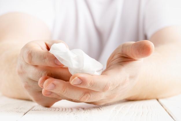De mens die haar handen met een natte alcohol schoonmaken veegt af