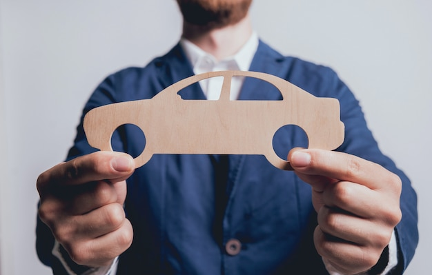 De mens die het ondertekenen van een autoverzekering voorstellen, agent houdt het houten automodel.