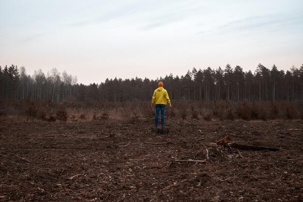 De mens die in een gele regenjas droeg, ziet het vernietigde bos na een technologische ramp