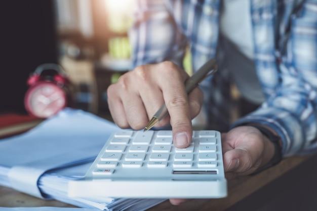 De mens die met financiën werken berekent op calculator en het gebruiken van computerlaptop en document gegevensgrafiek in bureauruimte.