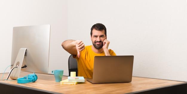 De mens die met laptot in een bureau werkt die duim toont ondertekent neer met negatieve uitdrukking