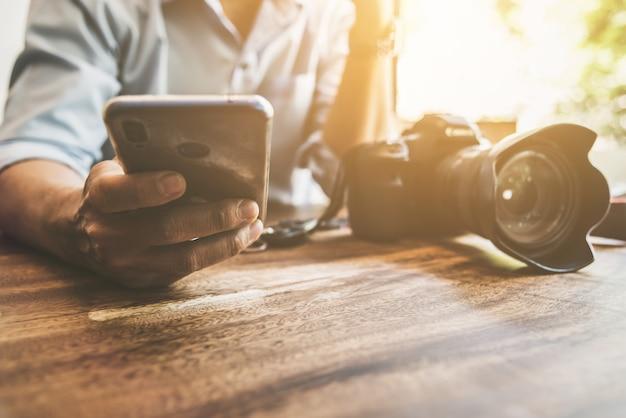 De mens die slimme mobiele telefoon met behulp van voor verbindt met vrienden in koffiewinkel