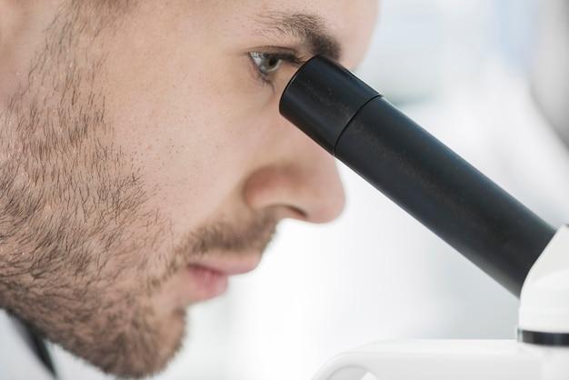 De mens die van de close-up microscoop bekijkt