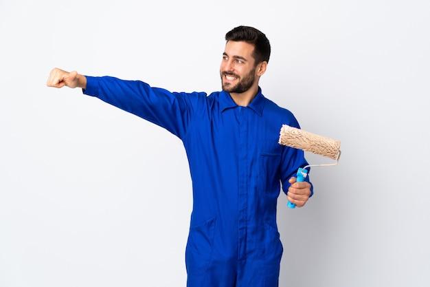 De mens die van de schilder een verfrol houdt die op witte muur wordt geïsoleerd die duimen op gebaar geven