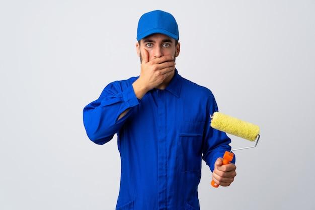 De mens die van de schilder een verfrol houdt die op witte muur wordt geïsoleerd die mond behandelt met hand
