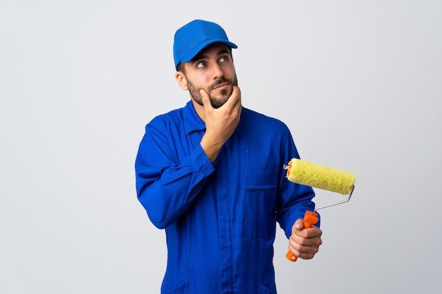 De mens die van de schilder een verfrol houdt die op witte muur wordt geïsoleerd die twijfels heeft en met gezichtsuitdrukking verwart