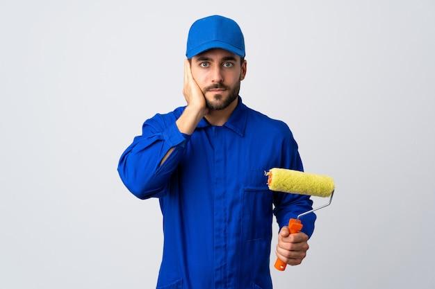 De mens die van de schilder een verfrol houdt die op witte muur wordt geïsoleerd frustreerde en oren behandelt