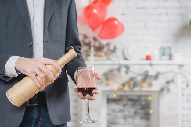 De mens die van het gewas rode wijn in glas giet