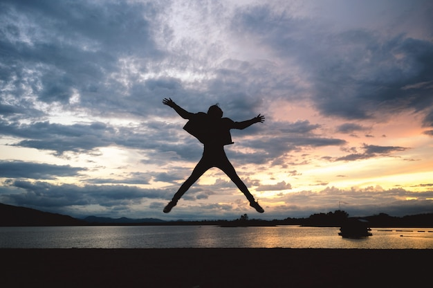 De mens die van het silhouetgeluk op meer bij zonsondergang springen