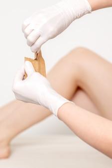 De mens dient beschermende handschoenen in die ambachtelijke envelop met medische of schoonheidshulpmiddelen houden