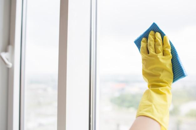 De mens dient gele handschoen in die het glas van venster schoonmaakt. het doet dit met blauwe doek. het is dag buiten.