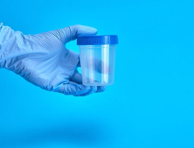 De mens dient latex steriele handschoenen in die een lege plastic kruik voor medische tests houden