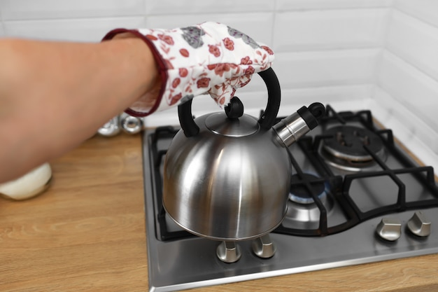 De mens dient vuisthandschoenen in houdend metaalketel in de keuken.