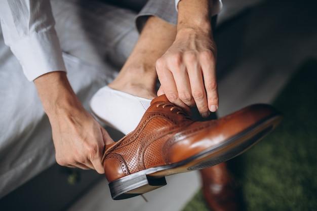 De mens draagt binnenshuis schoenen.
