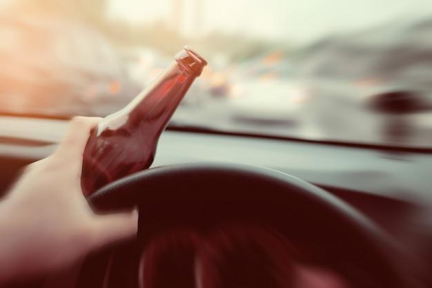 De mens drinkt bier terwijl het drijven van auto, rijdend in een staat van bedwelming, drink niet en drijf concept