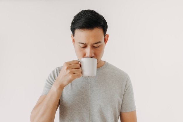De mens drinkt koffie of thee die op witte achtergrond wordt geïsoleerd
