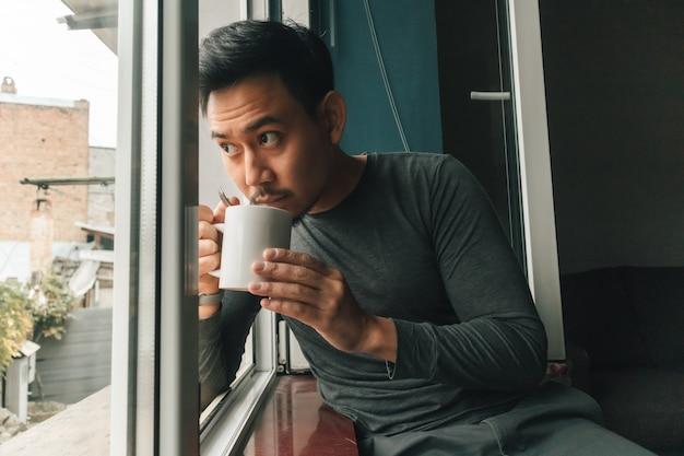 De mens drinkt warme koffie en voelt zich ontspannen bij de ramen.