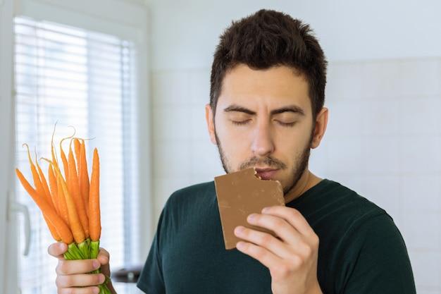 De mens eet chocolade met veel plezier. hij wil geen groenten eten.