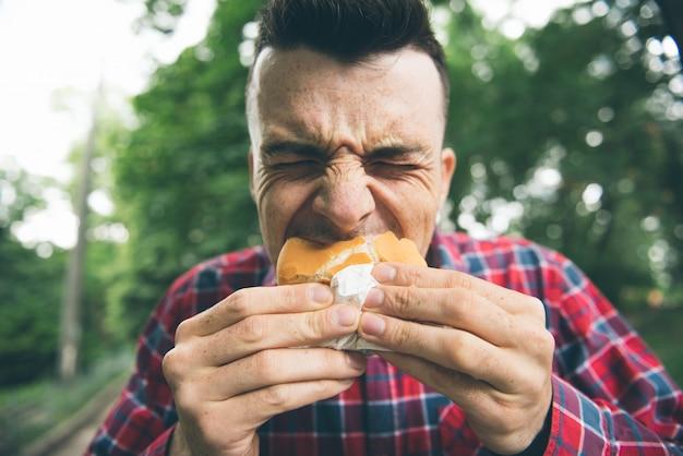 De mens eet in het park en geniet van heerlijk eten