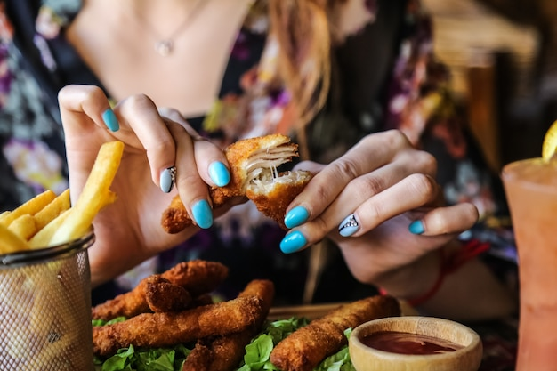 De mens eet kippenvingers met het zijaanzicht van de frietenketchup