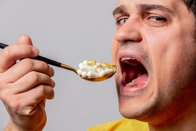 De mens eet pillen met lepel