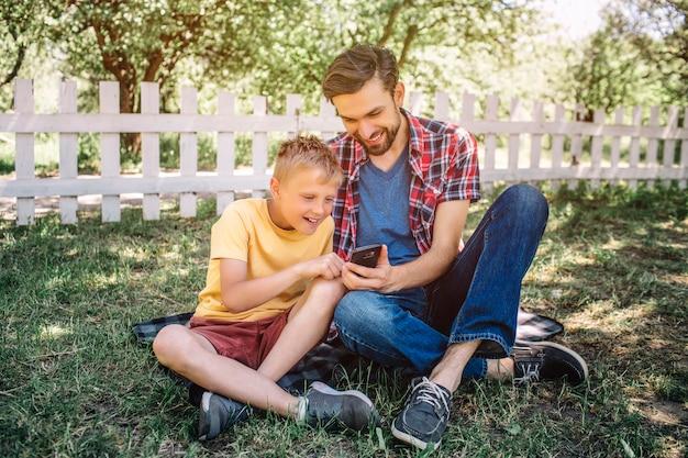 De mens en het kind zitten samen op gras met hun benen gekruist en bekijken telefoon