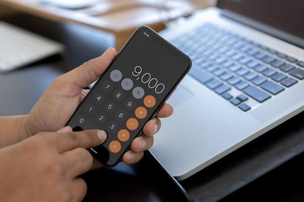 De mens gebruikt calculator om kosten in bureau te berekenen