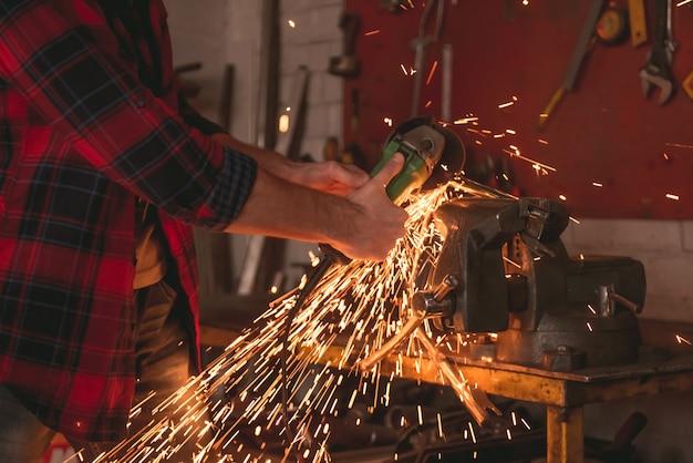 De mens gebruikt een hoekmolen terwijl het werken in reparatiewerkplaats.