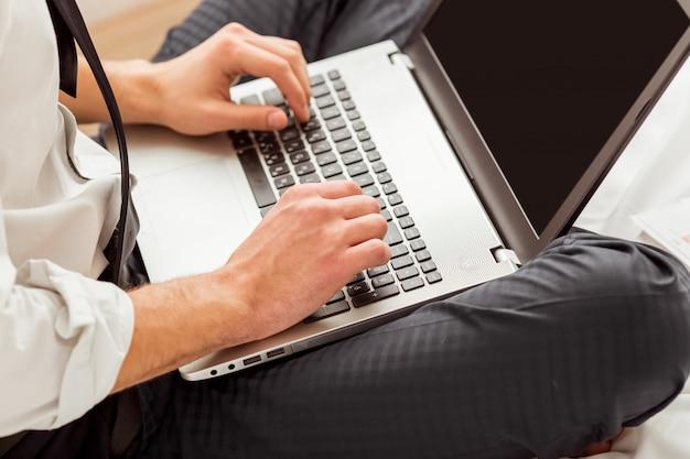 De mens gebruikt laptop terwijl hij met gekruiste benen op bed zit.
