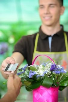 De mens geeft creditcard aan klant na aankoop.