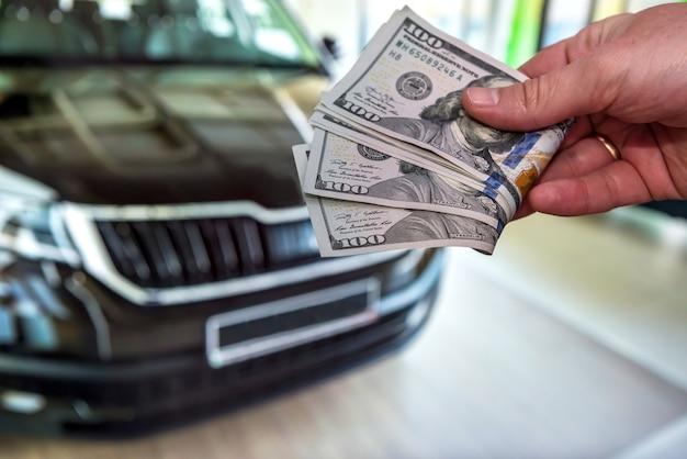 De mens geeft dollar als betaling voor de aankoop of reparatie van een auto. concept aankoop nieuwe moderne auto