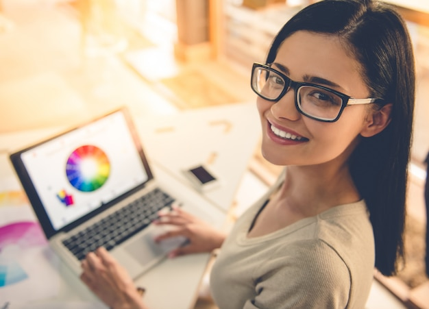 De mens glimlacht terwijl het werken met laptop in haar studio