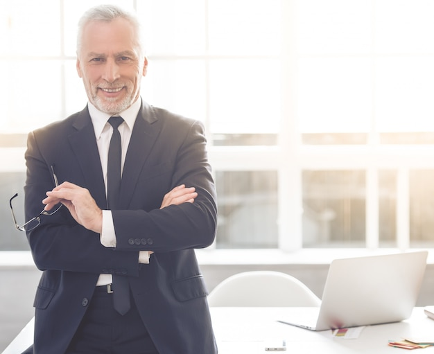 De mens glimlacht terwijl status in zijn kantoor