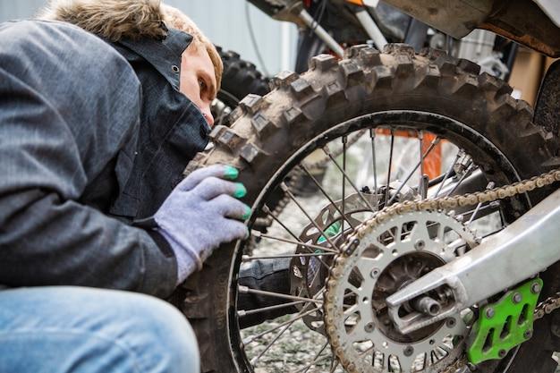 De mens haalt een wiel vast aan een motorfiets dicht omhoog