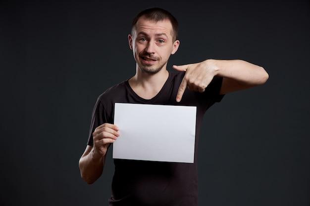 De mens heeft een leeg blad van posterpapier in zijn handen. glimlach en vreugde, plaats voor tekst, kopieer ruimte