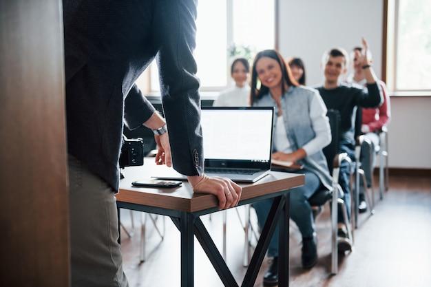 De mens heeft een vraag. hand opgestoken. groep mensen op handelsconferentie in moderne klas overdag